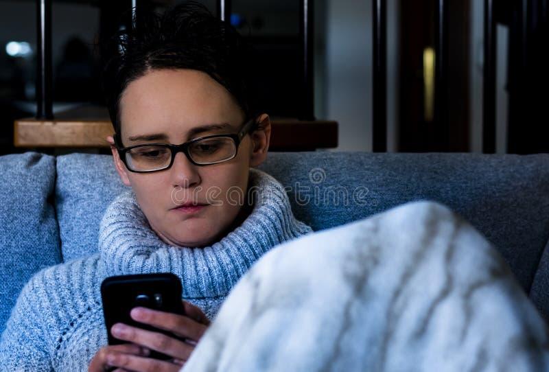 Mulher que usa o telefone celular e a cobertura pretos fotografia de stock