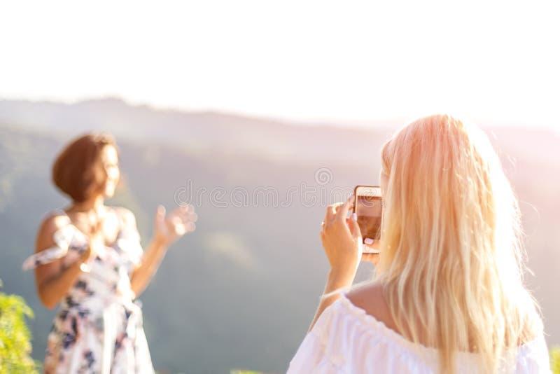 Mulher que usa o telefone celular e tomando fotos do seu sorriso encaracolado imagem de stock
