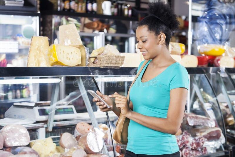 Mulher que usa o telefone celular na loja de mantimento imagem de stock