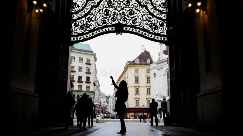 Mulher que usa o telefone celular no hofburg Viena, silhueta, ângulo largo fotografia de stock royalty free