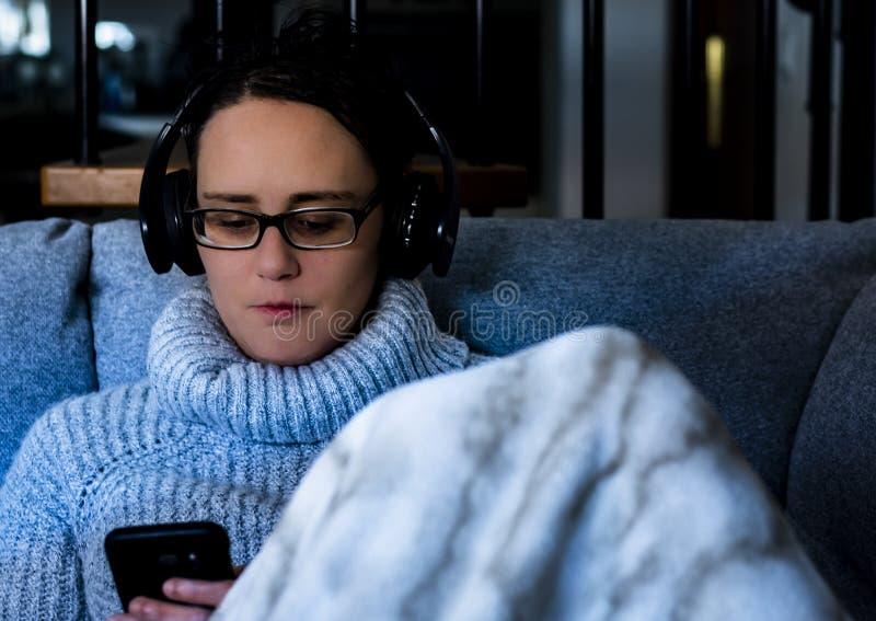 Mulher que usa o telefone celular preto, fones de ouvido pretos e cobertura fotografia de stock royalty free
