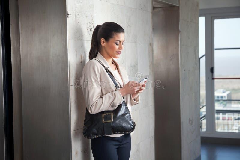 Mulher que usa o telefone de pilha fotografia de stock