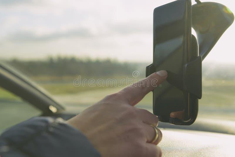 Mulher que usa o telefone do smort ao conduzir o carro foto de stock