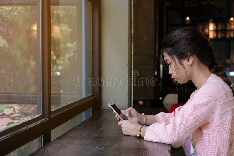 Mulher que usa o telefone esperto na tabela, em povos e no conceito de madeira da tecnologia fotografia de stock royalty free