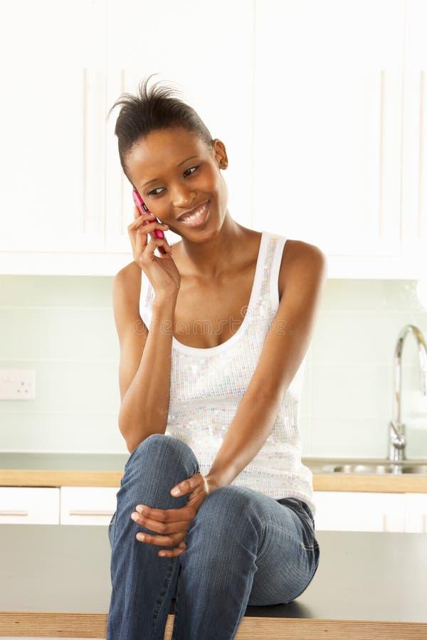 Mulher que usa o telefone móvel que senta-se na cozinha fotografia de stock