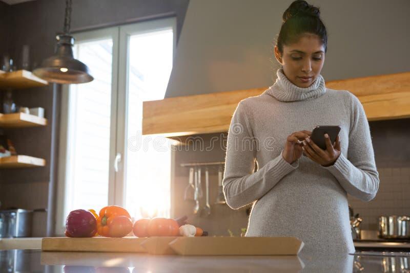 Mulher que usa o telefone na cozinha foto de stock royalty free