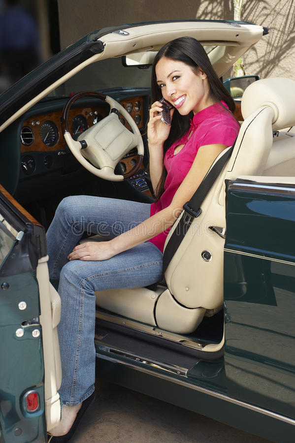 Mulher que usa o telemóvel em um Convertible imagens de stock royalty free