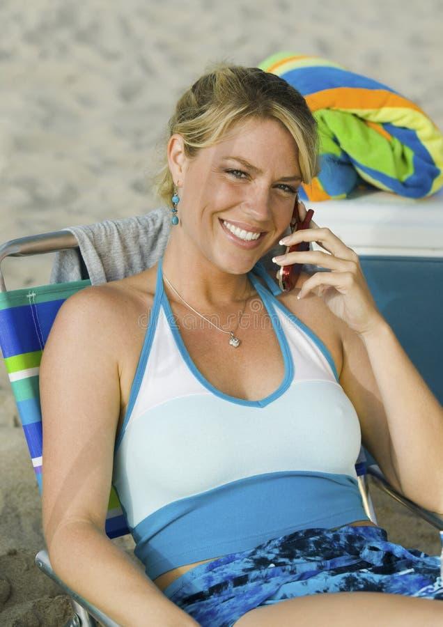 Mulher que usa o telemóvel na praia imagem de stock royalty free