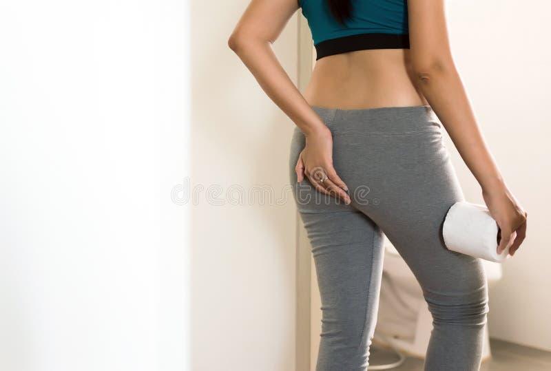 A mulher que usa o toalete e sofre da diarreia com papel higiênico após acorda na manhã foto de stock royalty free