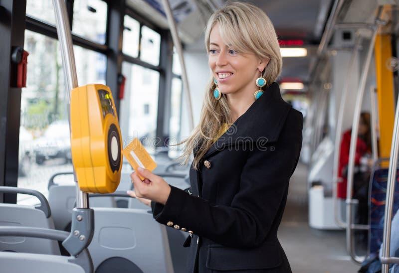 Mulher que usa o transporte eletrônico da máquina de perfuração do bilhete em público imagem de stock royalty free