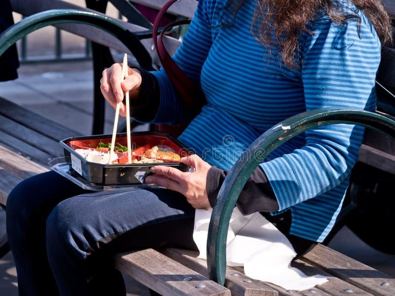 Mulher que usa os hashis que comem o almoço no banco imagem de stock royalty free