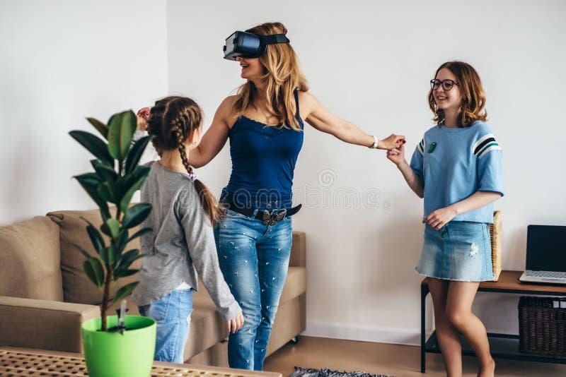 Mulher que usa a realidade virtual dos vidros dos auriculares de VR em casa que está na sala de visitas com crianças fotografia de stock royalty free