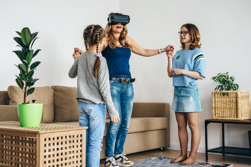 Mulher que usa a realidade virtual dos vidros dos auriculares de VR em casa que est? na sala de visitas com crian?as imagem de stock royalty free