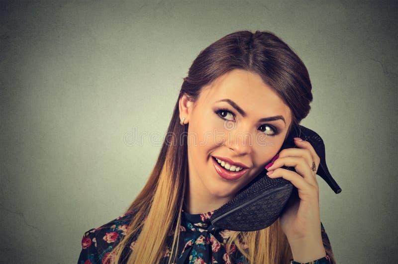 Mulher que usa a sapata como o telefone imagens de stock