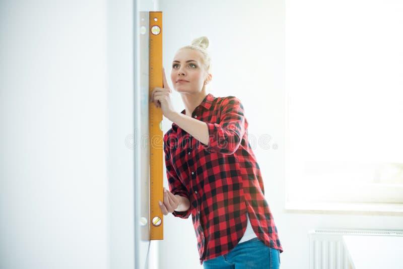 Mulher que usa-se nivelando a ferramenta em casa imagens de stock royalty free