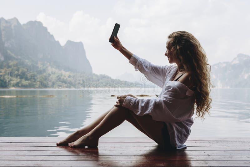 Mulher que usa seu telefone por um lago imagem de stock