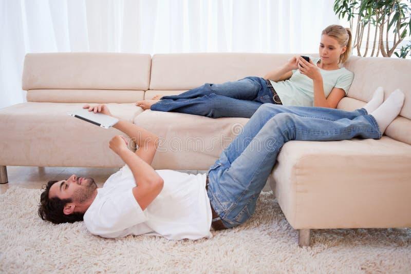 Mulher que usa seu telefone quando seu marido usar uma tabuleta imagens de stock