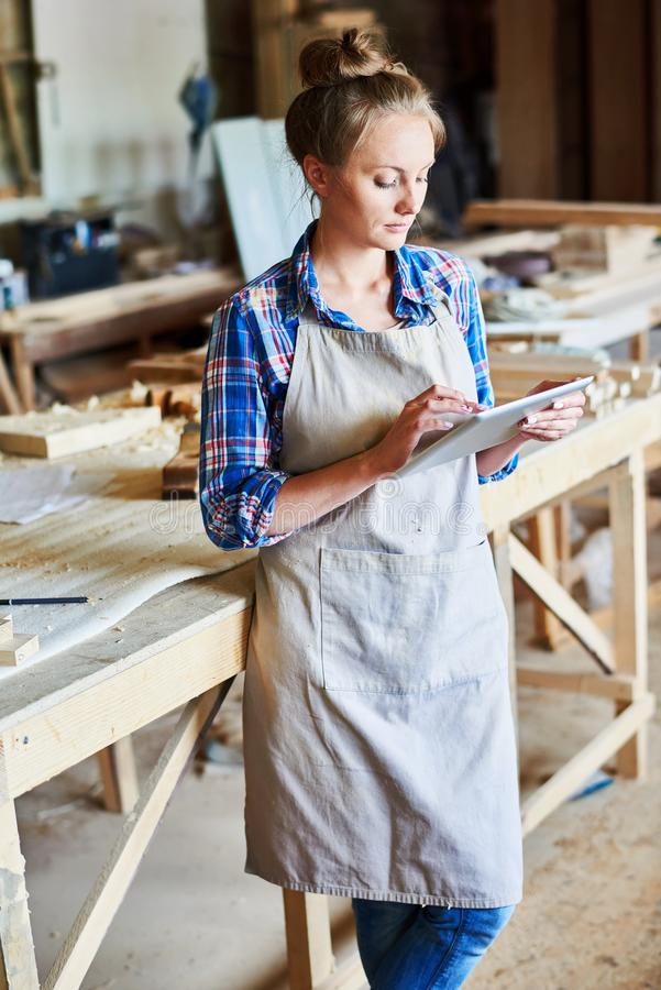 Mulher que usa a tabuleta de Digitas na loja das carpintarias foto de stock