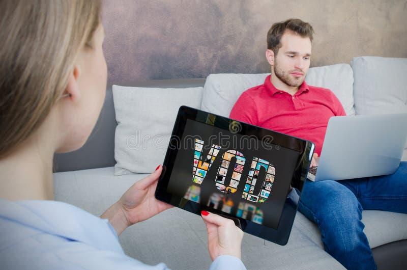 Mulher que usa a tabuleta digital para o filme de observação no serviço de VOD foto de stock