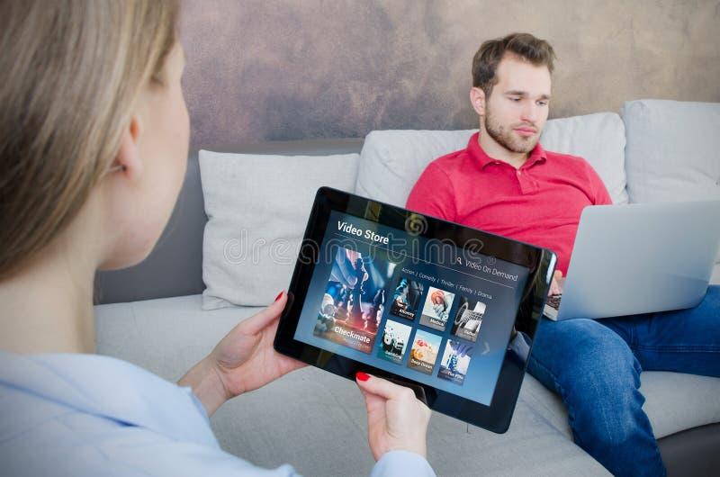 Mulher que usa a tabuleta digital para o filme de observação no serviço de VOD imagens de stock