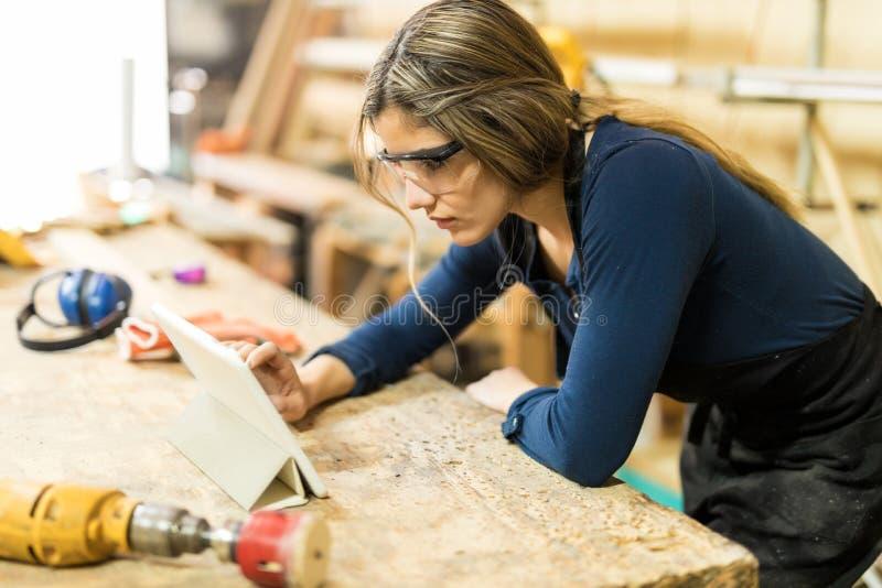 Mulher que usa a tabuleta em um woodshop imagens de stock