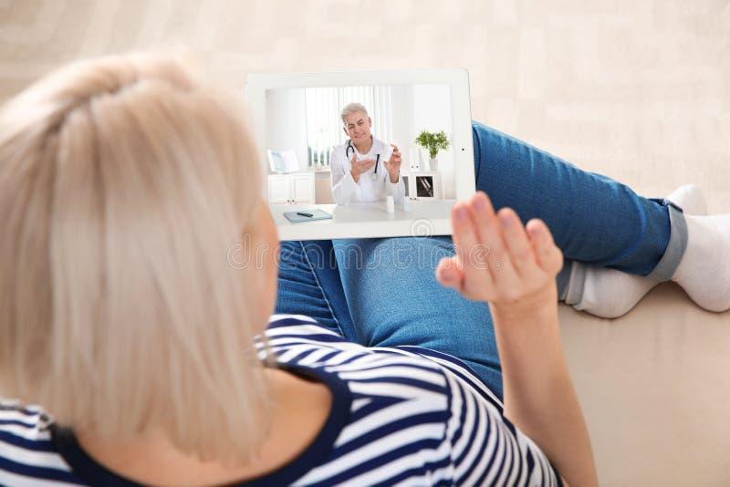 Mulher que usa a tabuleta para a consulta em linha com o doutor atrav?s do bate-papo video em casa foto de stock royalty free