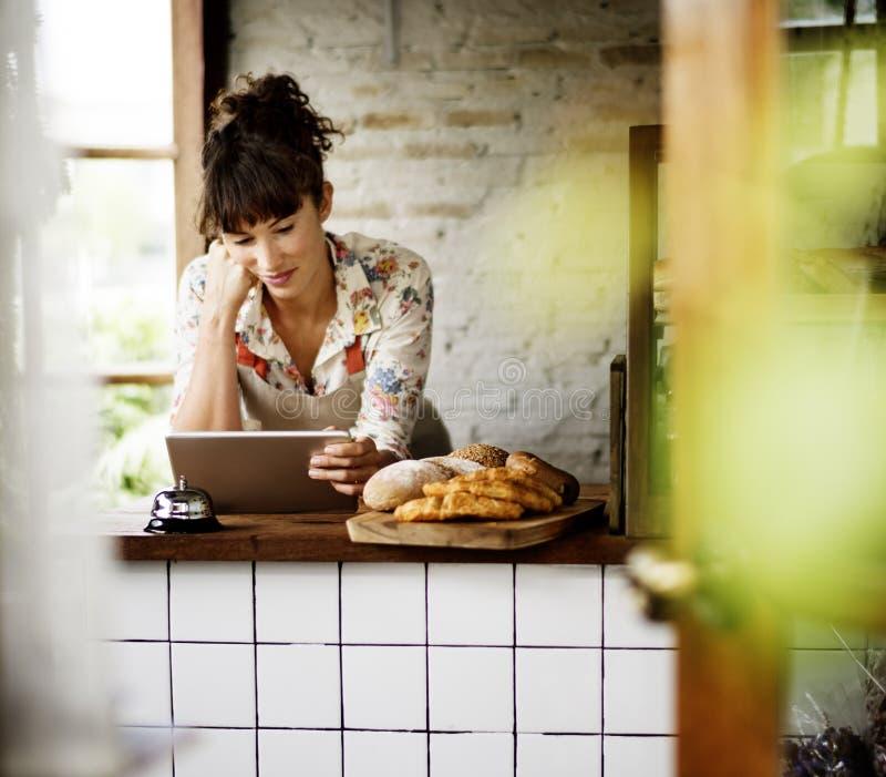 Mulher que usa a tabuleta para a ordem de negócio em linha imagem de stock