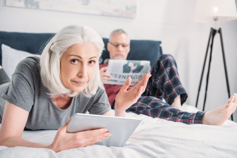 Mulher que usa a tabuleta quando jornal da leitura do marido imagem de stock royalty free