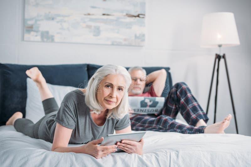 Mulher que usa a tabuleta quando jornal da leitura do marido fotografia de stock royalty free