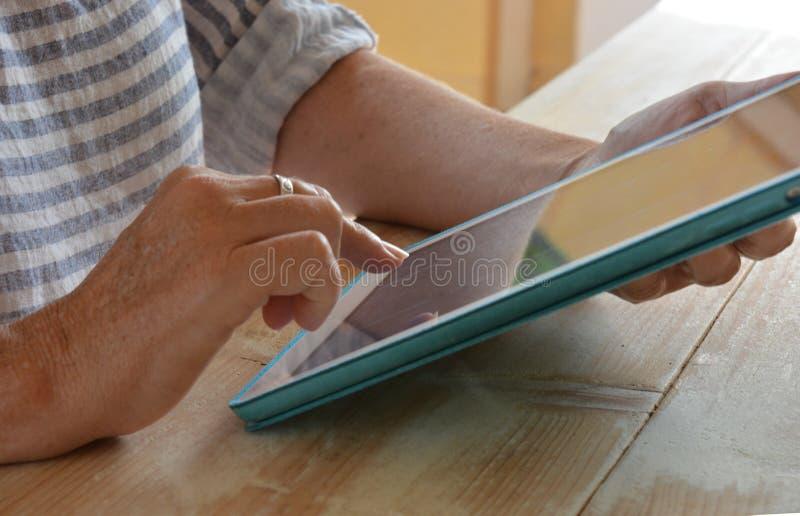 Mulher que usa a tecnologia, uma tabuleta, close-up das mãos fotos de stock