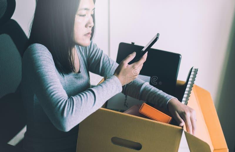 Mulher que usa telefone celular e equipamento de caixa de retenção do trabalho,Conceito de trabalho por desemprego fotografia de stock royalty free