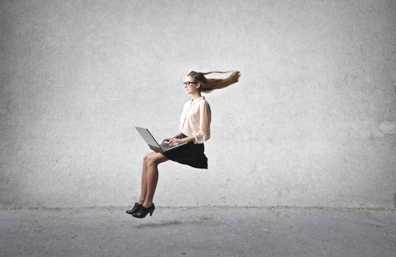 Mulher que usa um portátil foto de stock royalty free
