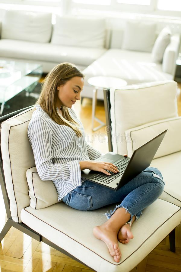 Mulher que usa um portátil ao relaxar no sofá na sala imagens de stock royalty free