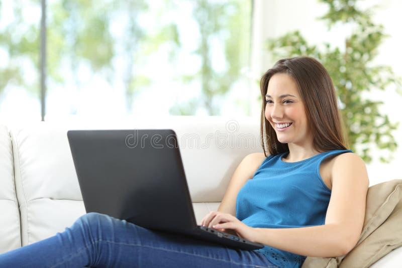 Mulher que usa um portátil que encontra-se no sofá foto de stock royalty free