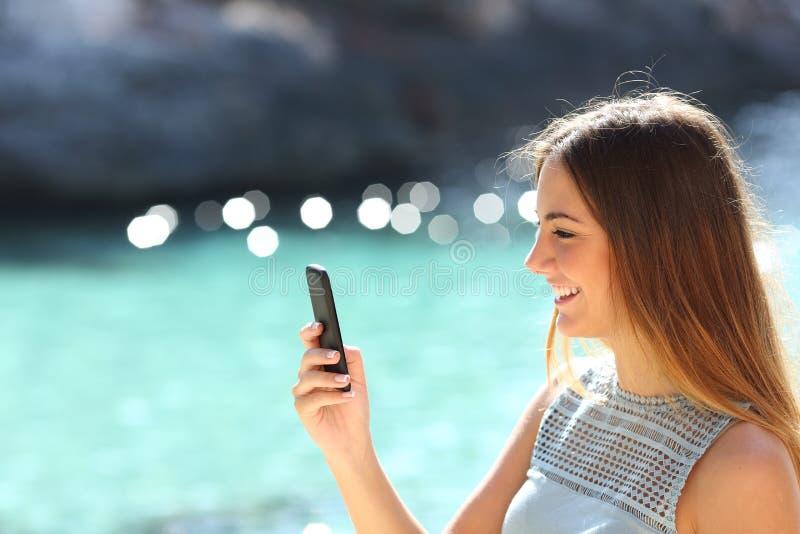Mulher que usa um telefone esperto em uma praia tropical nas férias fotografia de stock royalty free