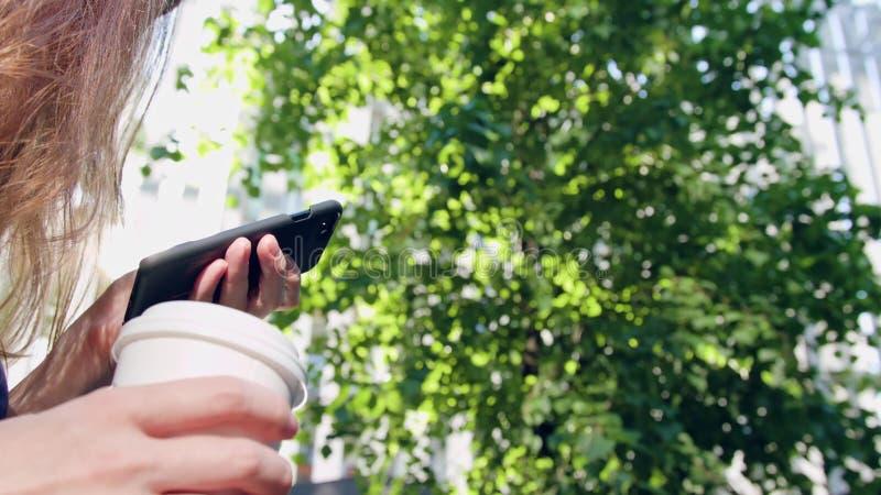 Mulher que usa um telefone no parque foto de stock