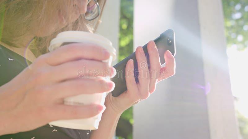 Mulher que usa um telefone no parque imagens de stock