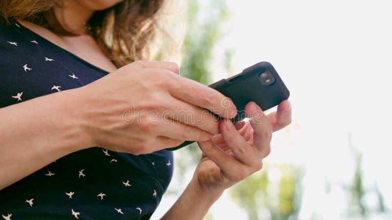 Mulher que usa um telefone no parque imagem de stock