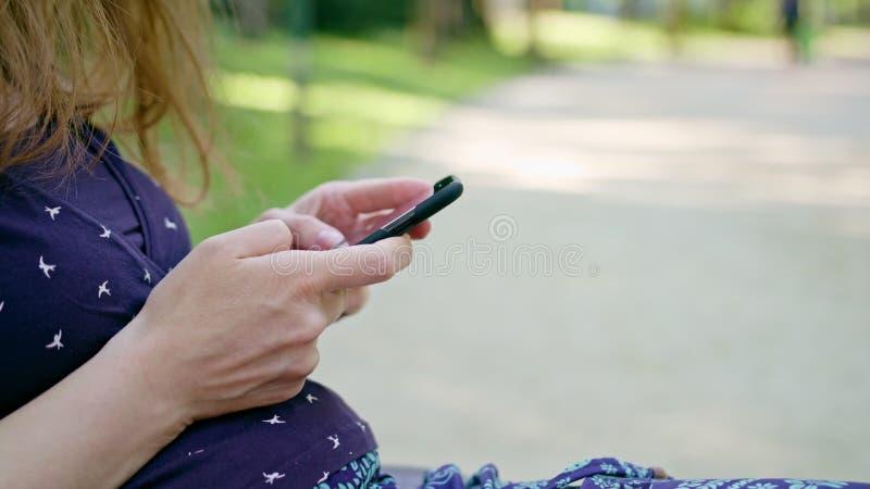 Mulher que usa um telefone no parque fotos de stock royalty free