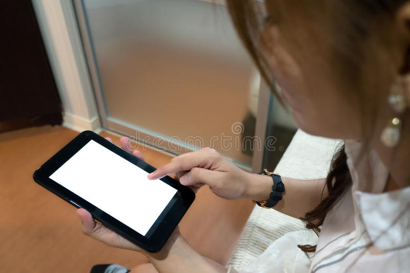 Mulher que usa uma tabuleta com a tela branca vazia fotografia de stock