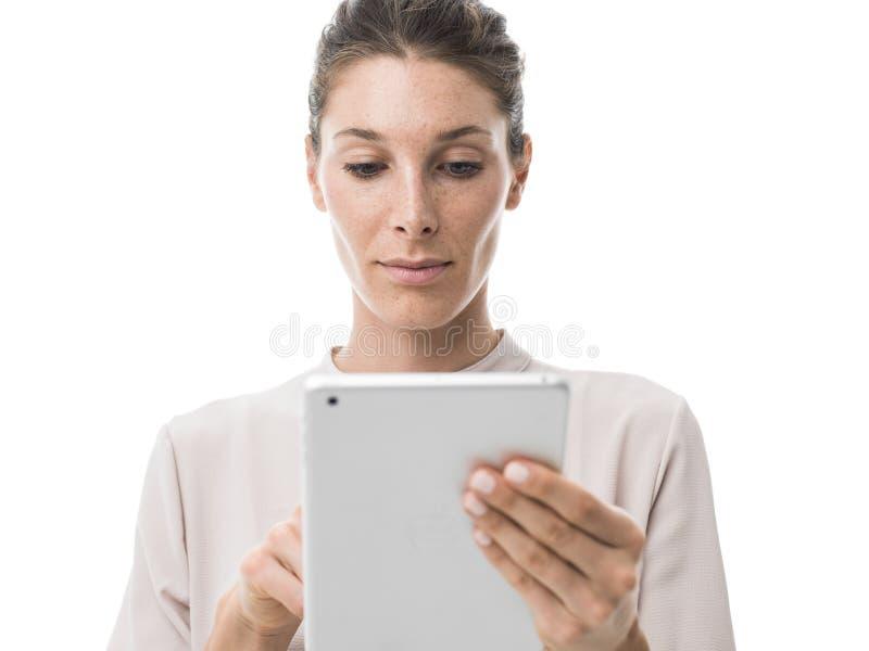 Mulher que usa uma tabuleta do tela táctil fotografia de stock