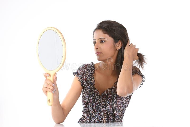 Mulher que vê seu penteado no espelho da composição foto de stock