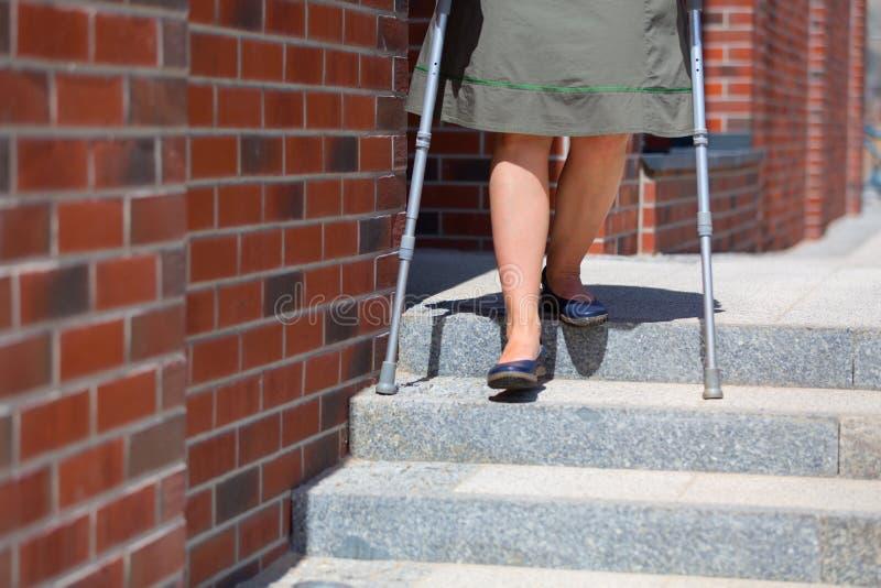 Mulher que vai abaixo das escadas usando muletas foto de stock