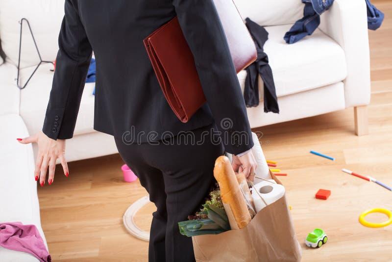 A mulher que vem em casa e vê a confusão imagem de stock
