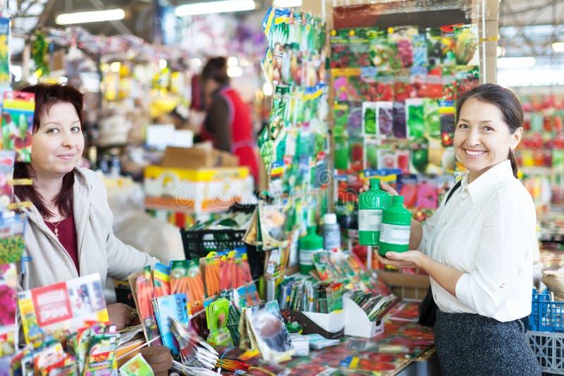 Mulher que vende o adubo líquido para amadurecer o comprador imagens de stock