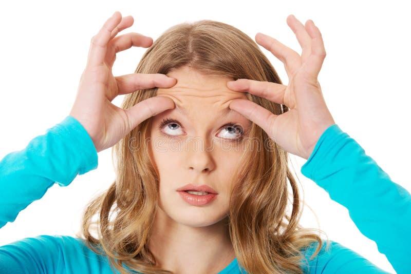 Mulher que verifica enrugamentos na testa imagem de stock royalty free