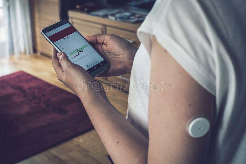Mulher que verifica o nível da glicose com um sensor remoto e um telefone celular, níveis da glicose do controle do sensor sem sa foto de stock