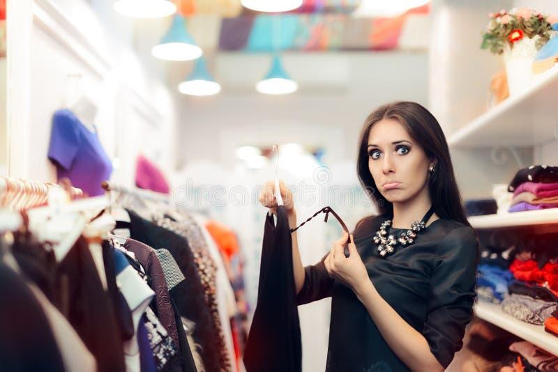 Mulher que verifica o preço na venda na loja de roupa foto de stock