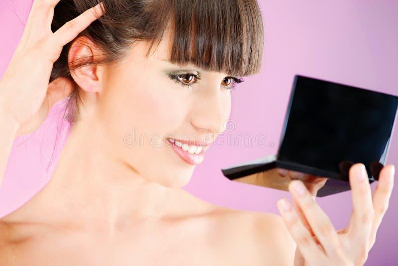 Mulher que verifica a pele da face no espelho fotos de stock