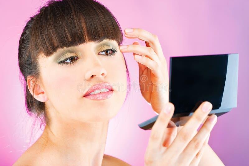 Mulher que verifica a pele da face no espelho imagem de stock